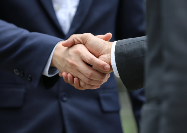 two men in business suit shaking hands